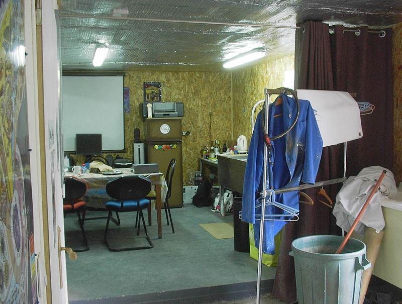Le salon - salle à manger - cuisine avec frigo et écran pour vidéoprojecteur