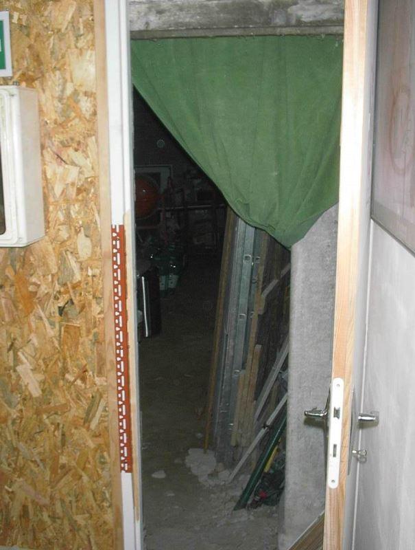 Au fond de la salle principale, l'entrée sur le local du milieu pas encore aménagé avec sol en terre battue, servant de stockage
