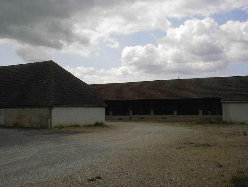 Aller vers ce hangar ouvert à bois et matériels et prendre à gauche