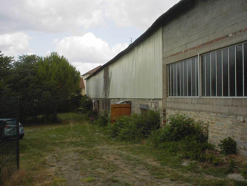 L'entrée principale du premier local est la première porte en bois, ouverte sur la photo